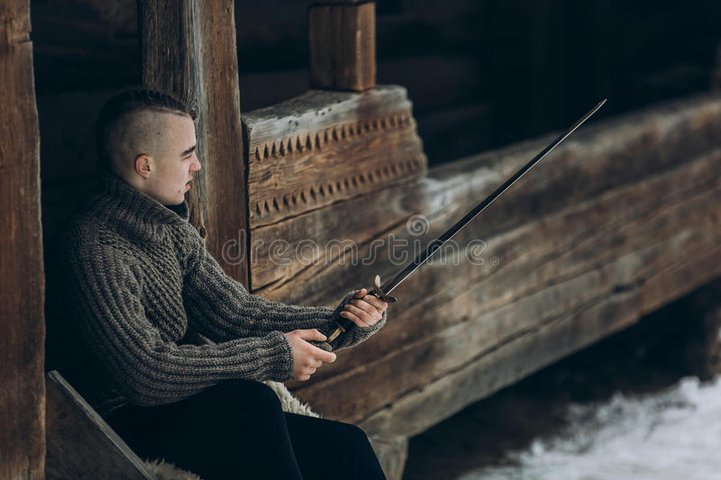 Brave warrior holding sword near historical wood castle building. In winter woods in Scandinavia, handsome viking with mohawk posing with weapon before battle royalty free stock photos
