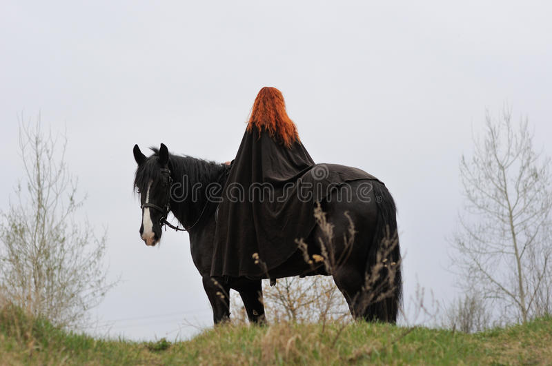 Brave woman with red hair in black cloak on friesian horse royalty free stock photos