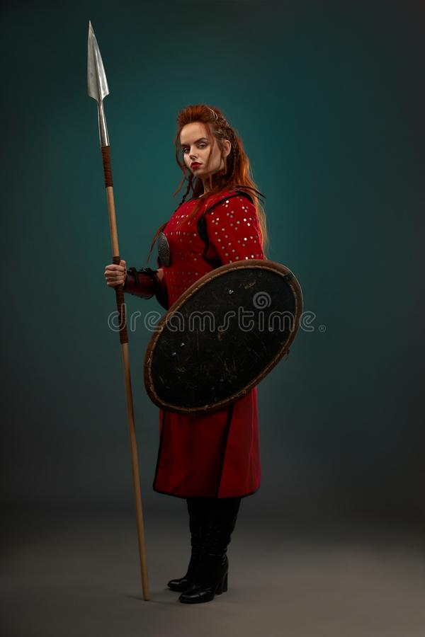 Brave woman warrior with weapon posing in studio. royalty free stock photos