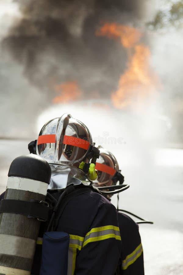 Bravez le feu mis par sapeur-pompier français avec de l'eau image libre de droits