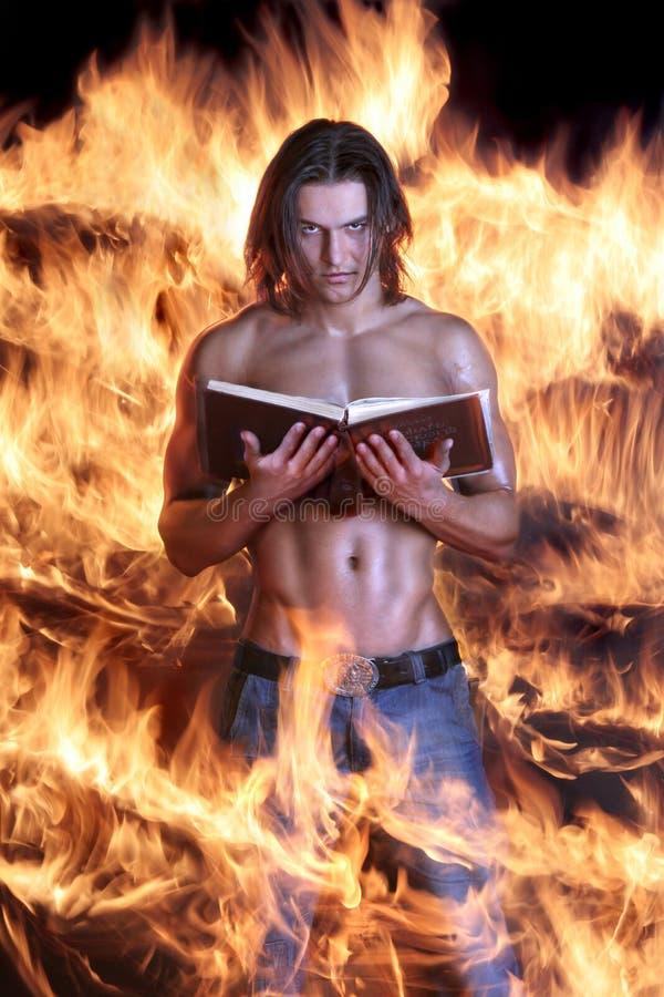 Brawny l'uomo tiene il libro e brucia su fuoco fotografia stock