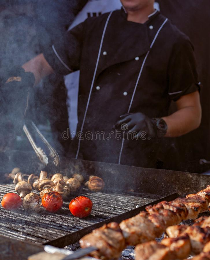 Brazier in a black tunic grills meat and vegetables by turning. Them over with iron tongs stock images
