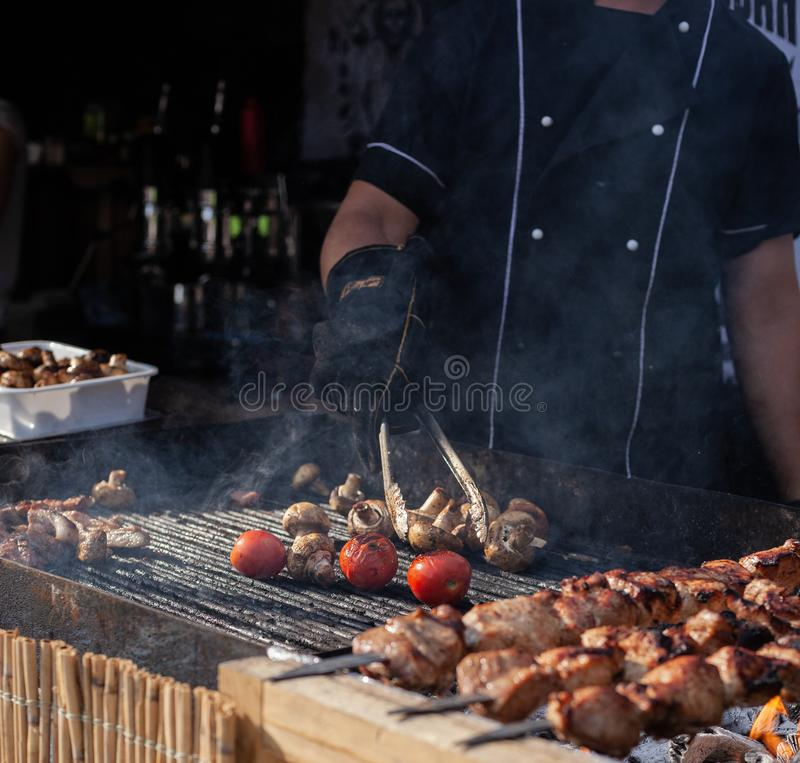 Brazier in a black tunic grills meat and vegetables. By turning them over with iron tongs royalty free stock image