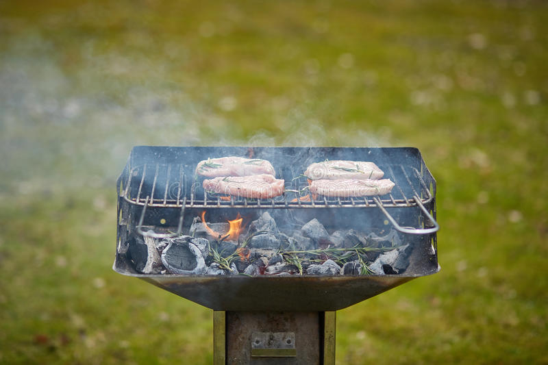 A brazier and four steaks on the grill royalty free stock images