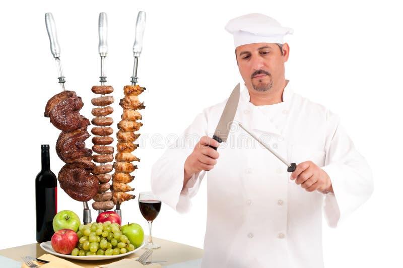 Chef preparing steak, sausage and chicken stock photography