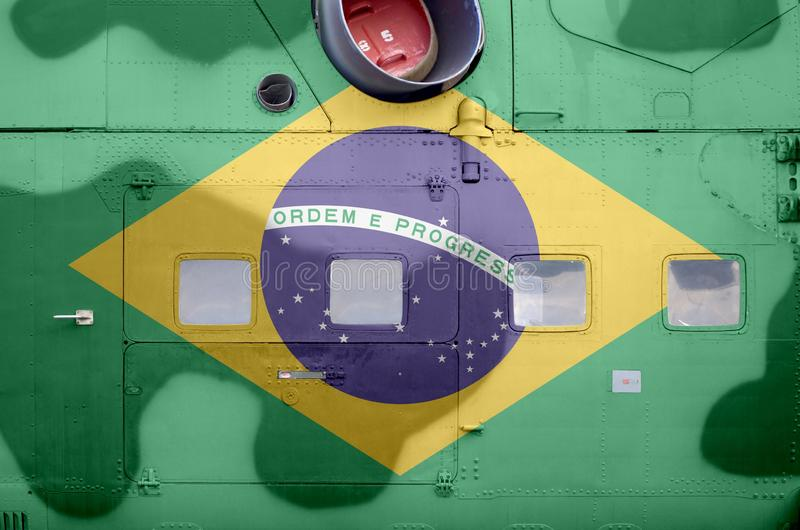 Brazil flag depicted on side part of military armored helicopter closeup. Army forces aircraft conceptual background. Brazil flag depicted on side part of royalty free stock images