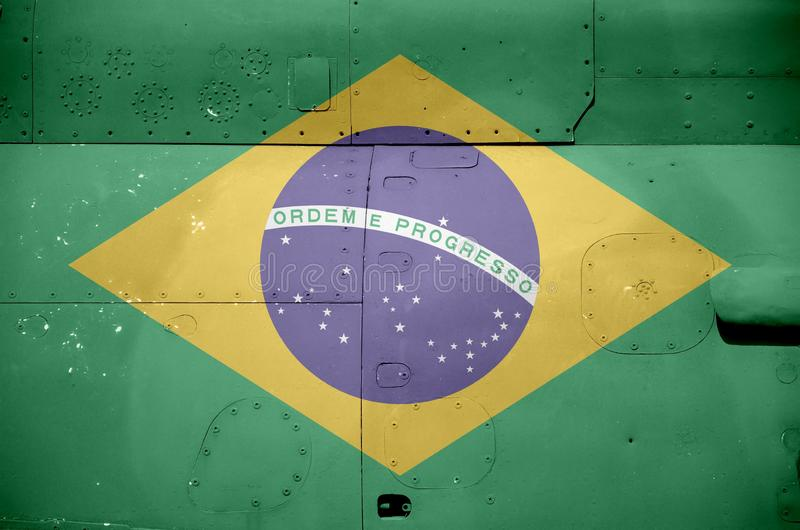 Brazil flag depicted on side part of military armored helicopter closeup. Army forces aircraft conceptual background. Brazil flag depicted on side part of stock image