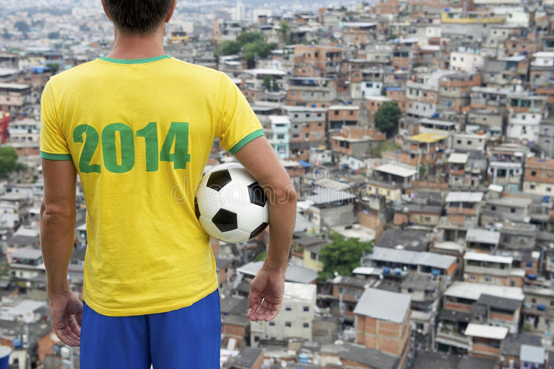 Brazil 2014 Football Player Standing with Soccer Ball Favela Rio. Brazilian football player standing in 2014 shirt holding soccer ball in front of favela royalty free stock images