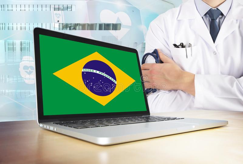 Brazil healthcare system in tech theme. Brazilian flag on computer screen. Doctor standing with stethoscope in hospital. Cryptocurrency and Blockchain concept stock image