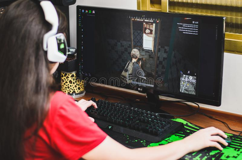 Gamer girl seated in front of the computer playing PUBG. royalty free stock photos