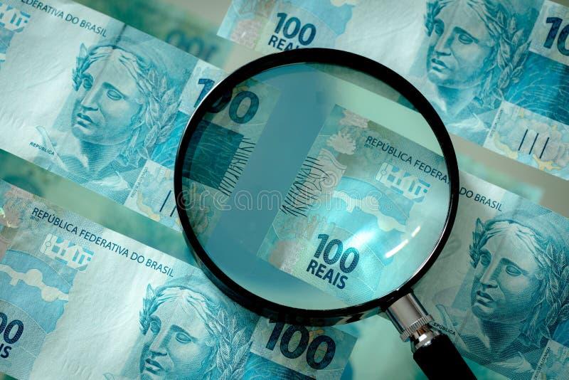 Braziliaans geld met een vergrootglas, honderd reaisbankbiljetten royalty-vrije stock foto's