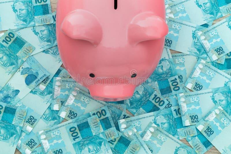Braziliaans geld, reais, en spaarvarken Het sparen en het deponeren geld royalty-vrije stock afbeelding