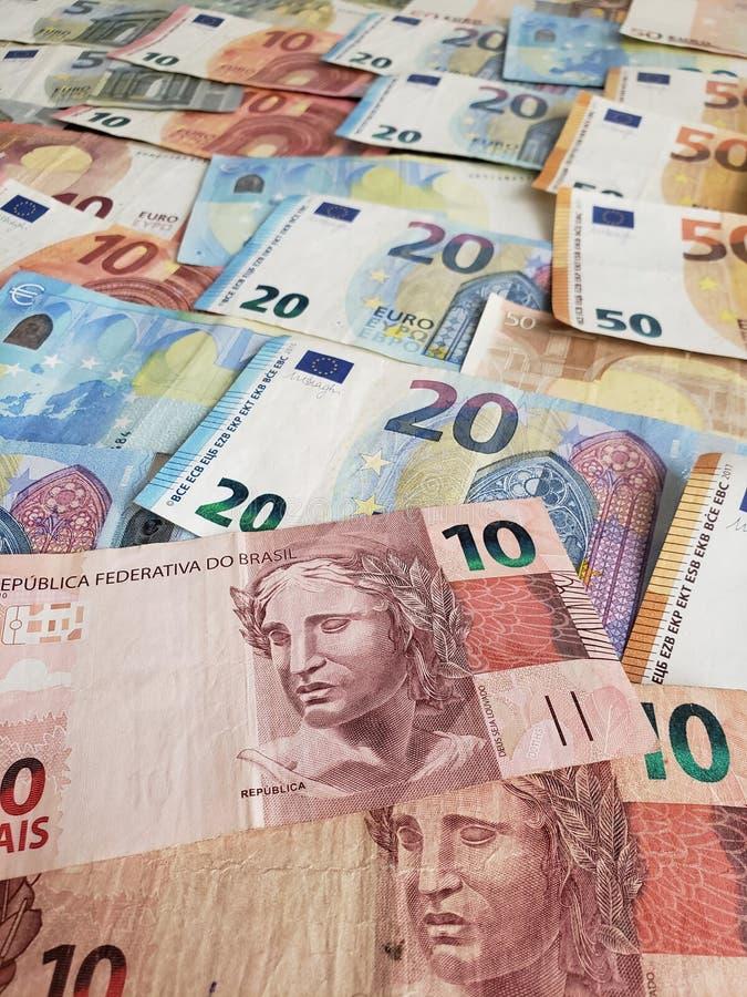 Braziliaanse bankbiljetten en Europese rekeningen van verschillende benamingen stock afbeeldingen