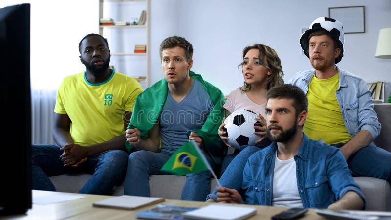 Braziliaanse groep vrienden die voetbal op spel op TV letten thuis, samenhorigheid royalty-vrije stock fotografie