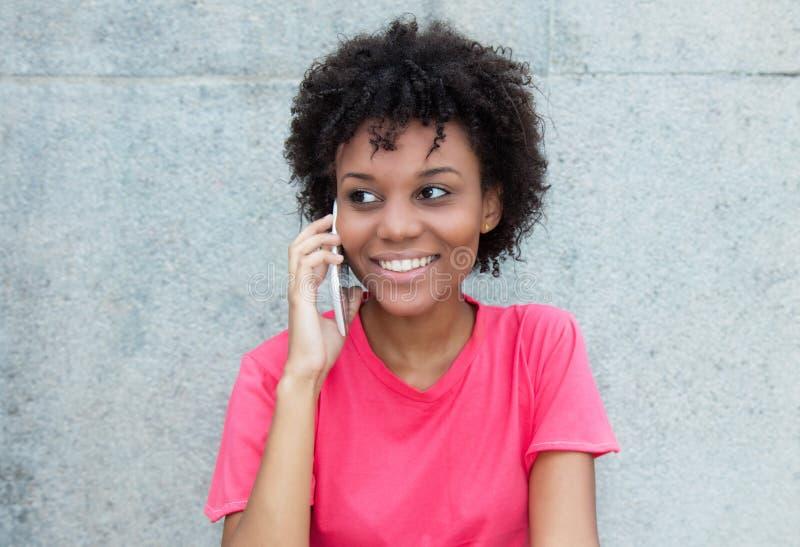 Braziliaanse vrouw in helder rood overhemd bij telefoon royalty-vrije stock afbeelding