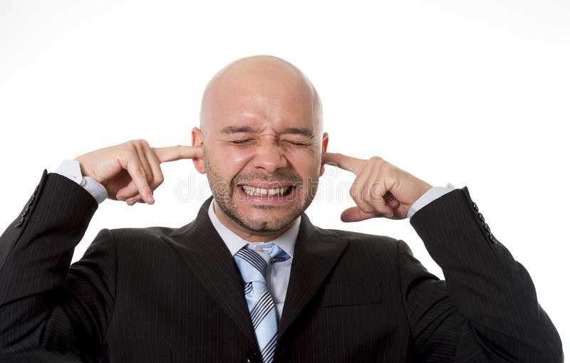 Brazilian businessman wearing suit and tie in stress covering his ears with fingers hoping for noise to stop royalty free stock image