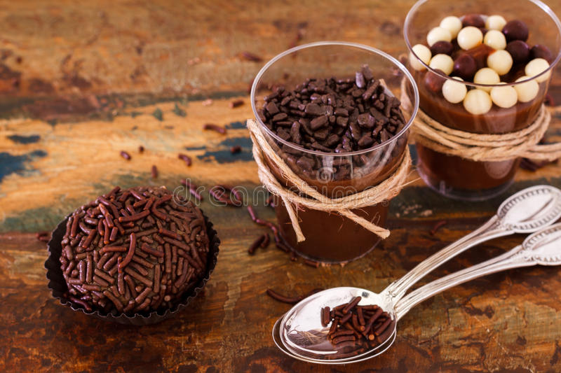 Brazilian chocolate bonbon truffle brigadeiro in glass. With spoon on wooden table stock image