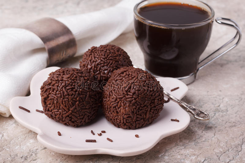 Brazilian chocolate truffle bonbon brigadeiro. On plate with cup of coffee on marble table. Selective focus royalty free stock photo