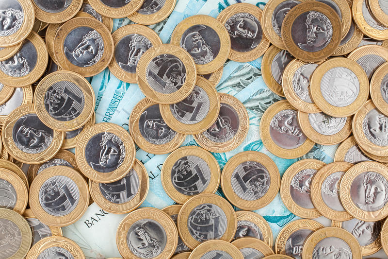 Brazilian coins and bank notes. Brazilian 1 Real coins and 100 Reais bank notes stock photo