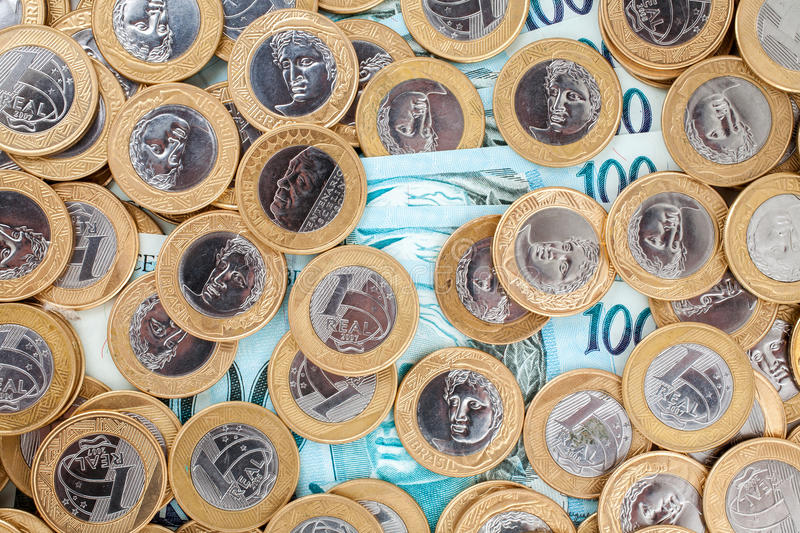 Brazilian coins and bank notes. Brazilian 1 Real coins and 100 Reais bank notes stock images