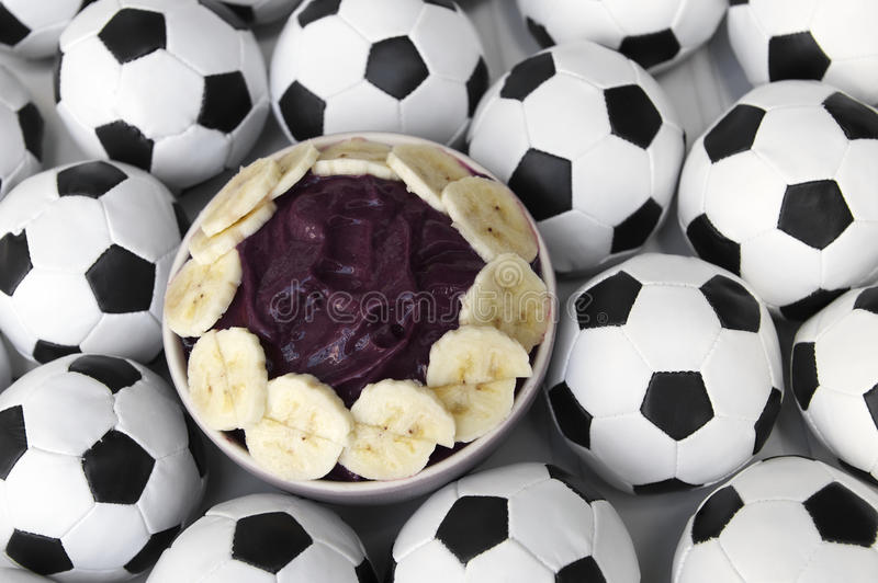 Brazilian Culture Acai and Football Soccer Balls. Brazilian culture on the table features a bowl of fresh acai with banana surrounded by football soccer balls stock photos