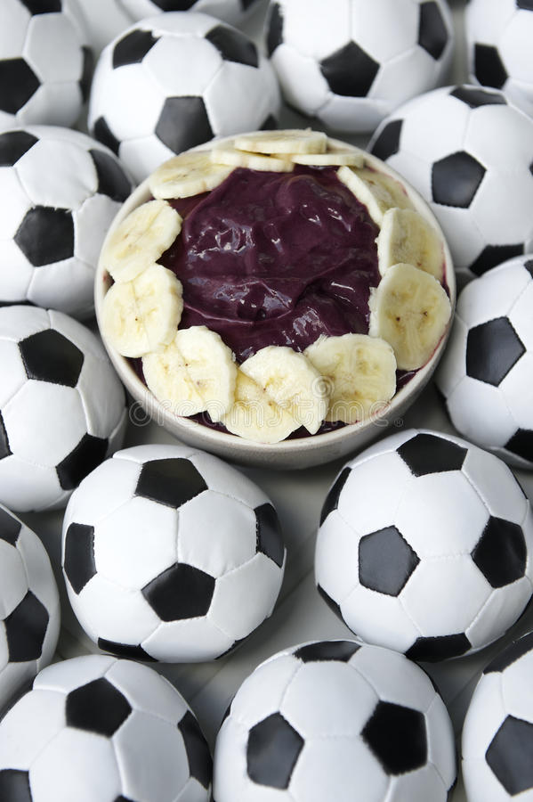 Brazilian Culture Acai and Football Soccer Balls. Brazilian culture on the table features a bowl of fresh acai with banana surrounded by football soccer balls stock photo