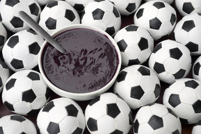 Brazilian Culture Acai and Football Soccer Balls. Brazilian culture on the table features a bowl of fresh acai surrounded by football soccer balls stock photography