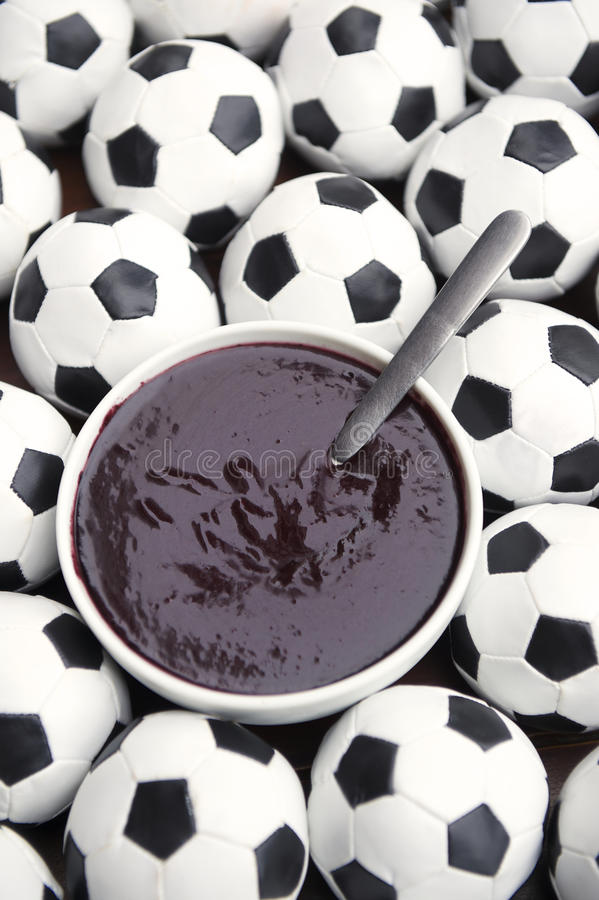 Brazilian Culture Acai and Football Soccer Balls. Brazilian culture on the table features a bowl of fresh acai surrounded by football soccer balls royalty free stock photography