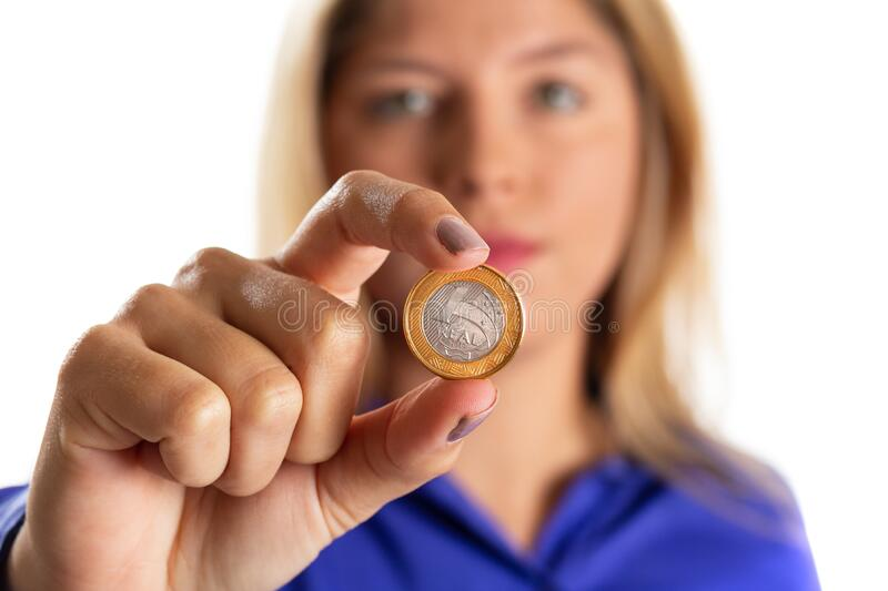 Brazilian Currency. Business woman holds coin at her fingertips. Economy in Brazil, monetary value of Real royalty free stock photography
