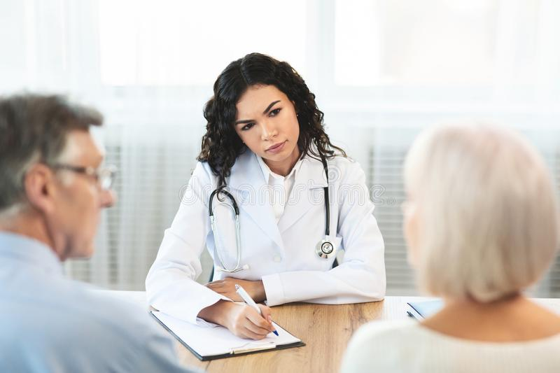 Brazilian doctor writing diagnosis consulting mature couple stock image