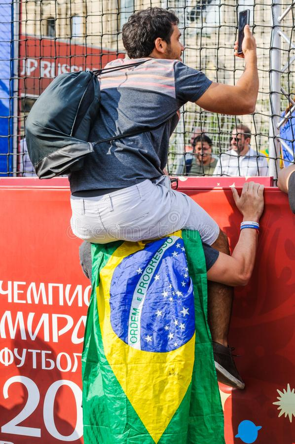 Brazilian fan sits on the shoulders of another and shoots a video on the smartphone what is happening in the fan zone. MOSCOW, RUSSIA - June 29, 2018: The 2018 stock images