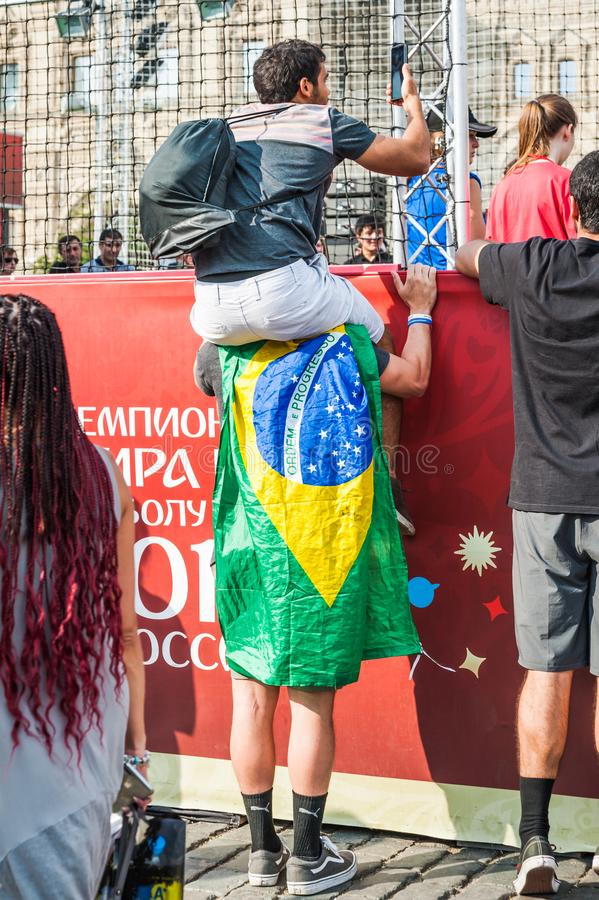 Brazilian fan sits on the shoulders of another and shoots a video on the smartphone what is happening in the fan zone. MOSCOW, RUSSIA - June 29, 2018: The 2018 stock photo