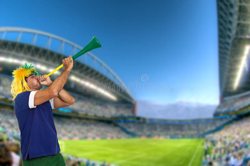 Brazilian fan at stadium playing vuvuzela royalty free stock image