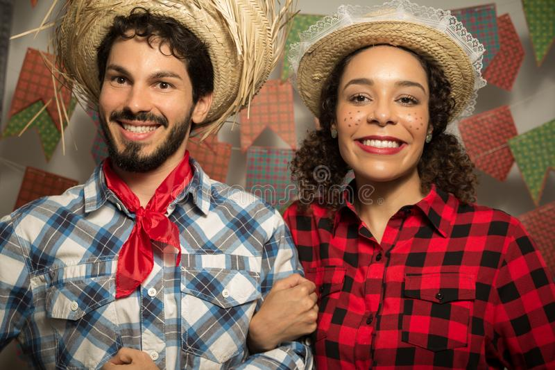 Festa Junina is June party in Brazil. Beautiful couple is holding hands and posing for the photo. They are wearing straw hats and royalty free stock images