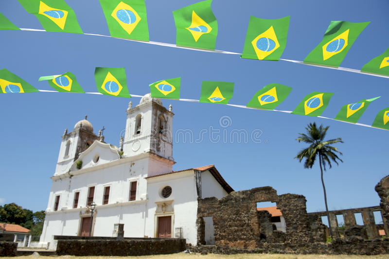 Brazilian Flag Bunting White Colonial Church Nordeste Brasil. Brazilian flag bunting flying over typical simple white colonial Carmo church with stone ruins in stock photo