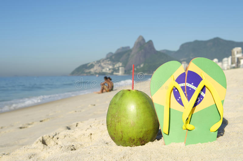 Brazilian Flag Flip Flops and Coconut Ipanema Beach Rio Brazil. Brazilian flag flip flops sandals stuck in the sand, with green coconut, on Ipanema Beach stock images