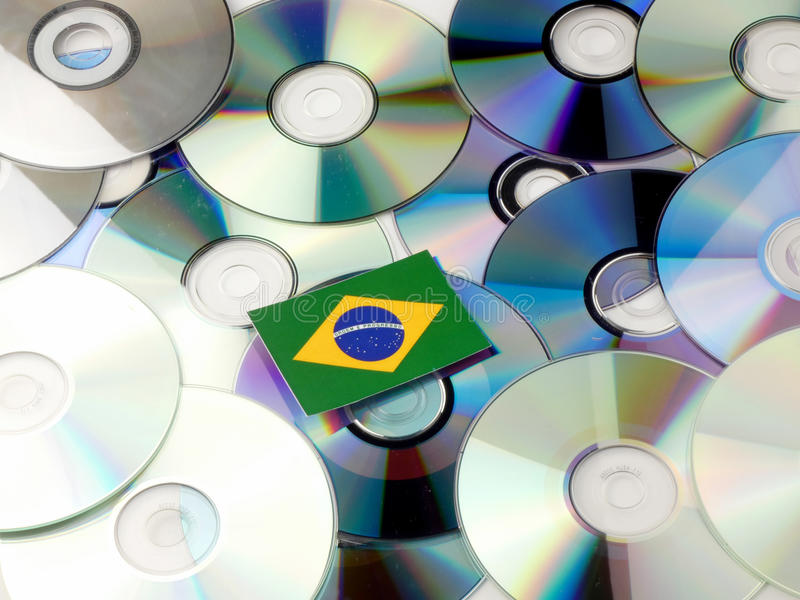 Brazilian flag on top of CD and DVD pile isolated on white stock image