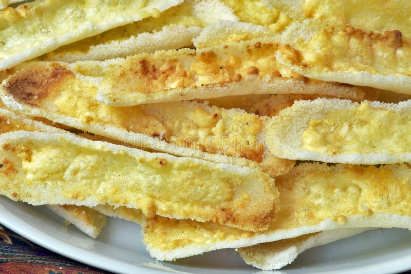 Brazilian food: crunchy beiju with butter. Brazilian food: crunchy beiju, type of dry pancake made from manioc starch, with butter, on table with colorful stock photography