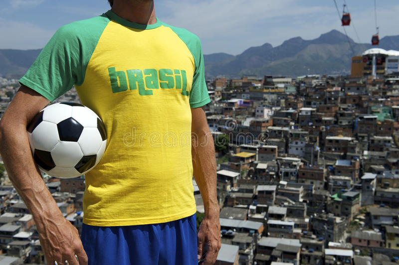 Brazilian Football Player Soccer Ball Rio Favela. Brazilian football player standing in Brazil colors holding soccer ball in front of favela slum background in stock images