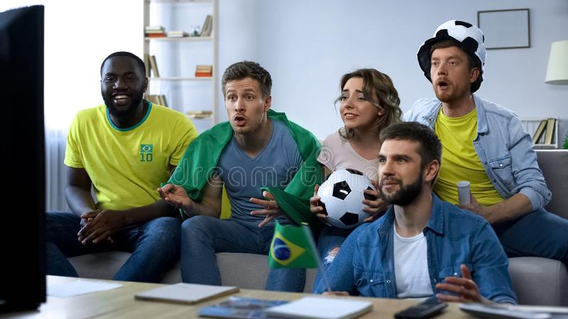 Brazilian friends watching match at home, supporting national football team royalty free stock photography