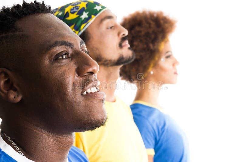 Brazilian group of fans celebrating on football match on white b. Brazil supporters. Brazilian group of fans celebrating on soccer / football match on white stock photo