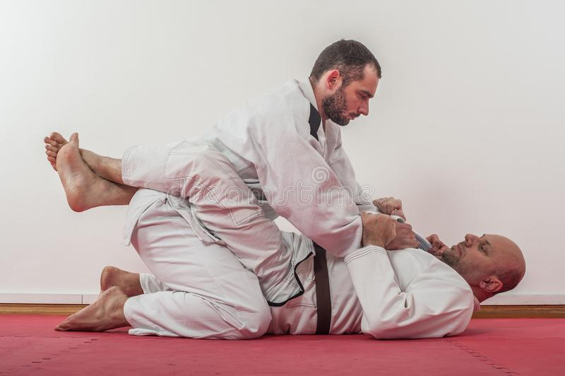 Brazilian jiu-jitsu training demonstration in traditional kimono. BJJ Closed guard position stock photos