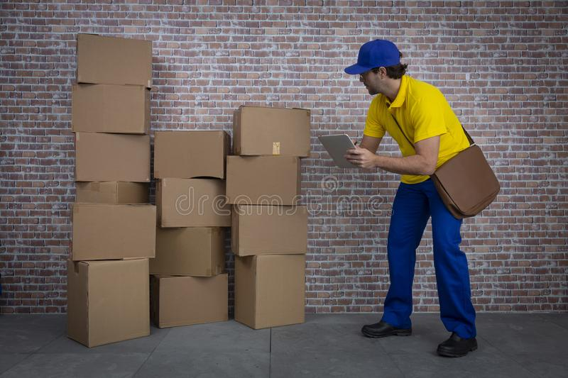 Brazilian mailman checking a lot of packages stock images