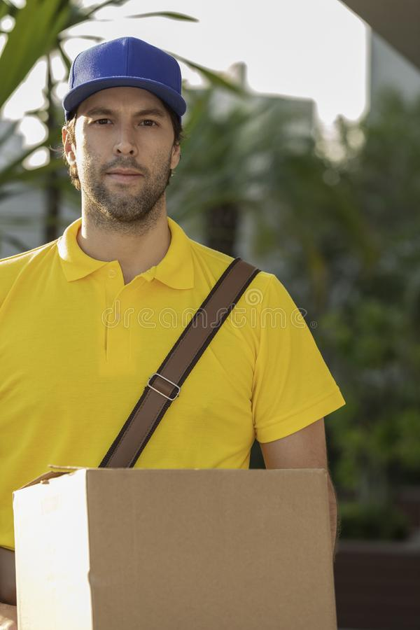 Brazilian mailman delivering a package. On the street. Internet purchase being delivered at home royalty free stock photography