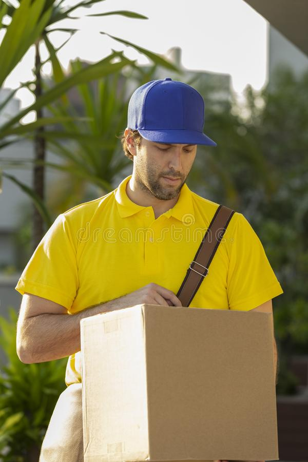 Brazilian mailman delivering a package. On the street. Internet purchase being delivered at home stock images