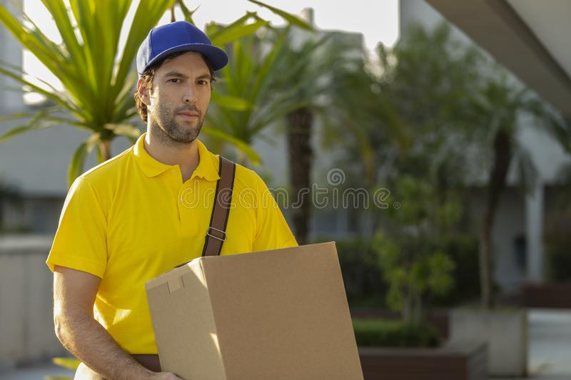 Brazilian mailman delivering a package. On the street. Internet purchase being delivered at home royalty free stock photos