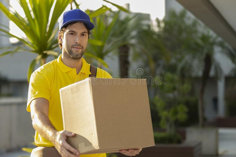 Brazilian mailman delivering a package. On the street. Internet purchase being delivered at home stock photography