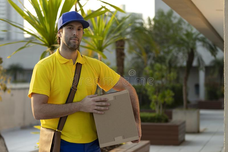Brazilian mailman delivering a package. On the street. Internet purchase being delivered at home stock photo