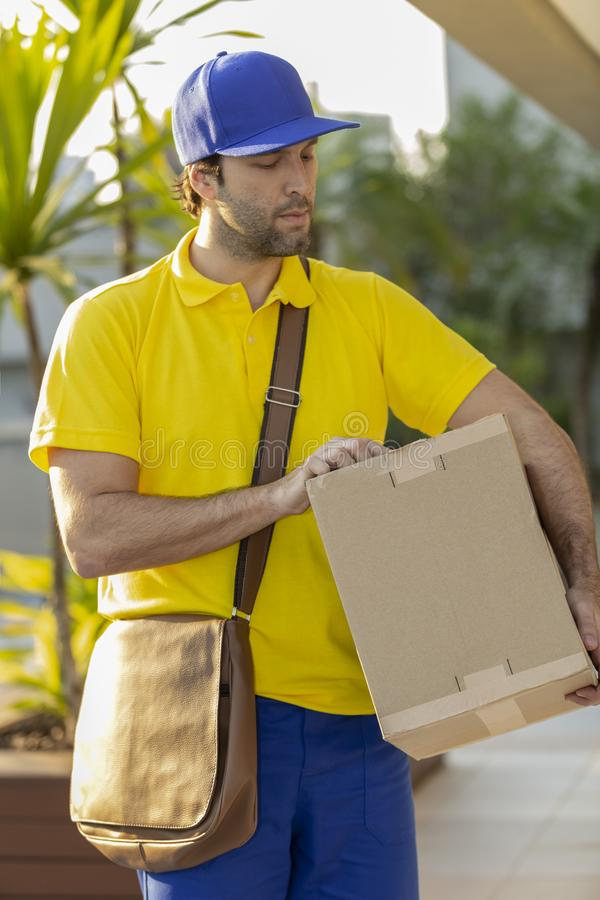 Brazilian mailman delivering a package. On the street. Internet purchase being delivered at home stock image