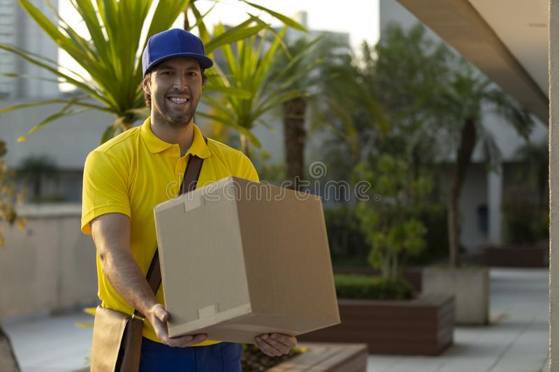 Brazilian mailman delivering a package. On the street. Internet purchase being delivered at home royalty free stock images